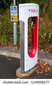 SARN, UNITED KINGDOM - AUGUST 2, 2018 : A  Tesla Supercharger and parking sign at the Sarn Park motorway services off the M4 near Bridgend in Wales.