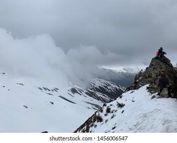 SARPASS, KASOL, HIMACHAL PRADESH, INDIA MAY 2019 Man sitting on top of sarpass enjoying weather and beautiful snowy mountains