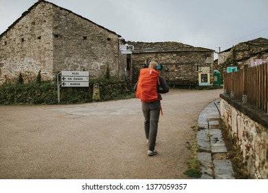 Sarria, Spain - April 7th, 2019: Camino de Santiago pilgrim walking with a backpack across a rural place in Galicia, Spain.