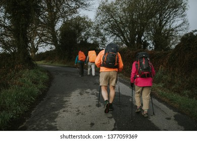 Sarria, Spain - April 7th, 2019: Camino de Santiago pilgrims walking with a backpack across a rural place in Galicia, Spain.