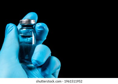 Sars-Kov-2 coronavirus vaccine in a transparent glass ampoule, covered with frost, on a dark background, short focus, toning  - Shutterstock ID 1961511952