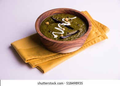 Sarson Ka Sag is a popular Punjabi curry recipe using mustard greens and spices. Served in a bowl and plate over moody background. selective focus