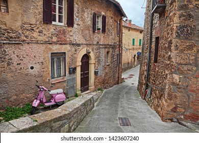 Sarteano, Siena, Tuscany, Italy - April, 7, 2019: picturesque ancient alley in the old town with a pink Vespa scooter