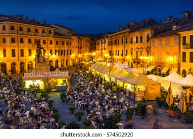 SARZANA, ITALY - AUGUST 10, 2015: People tasting traditional Italian food in the evening at the square - Piazza Giacomo Matteotti in Sarzana, Italy.