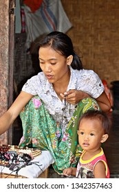 Sasak tribe woman with child.3th November 2010. Sade village. Lombok Island. Indonesia. Asia.