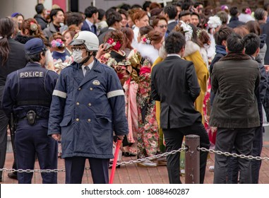 Sasebo, Japan - January 7, 2018:  Police watch over crowd during the coming of age day celebration in Japan.