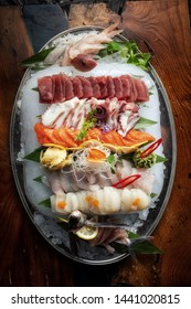 Sashimi from different types of fish on ice. Top view.
