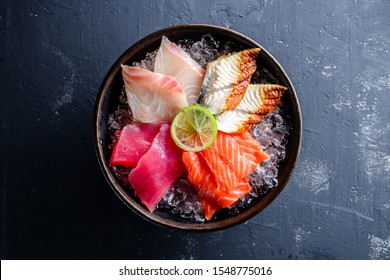 Sashimi japanese food, pieces of tuna, salmon, smoked eel with ice in bowl. Fish slices top view