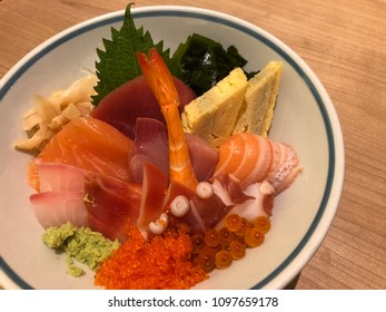 Sashimi rice bowl on wood table in Japanese restaurant.