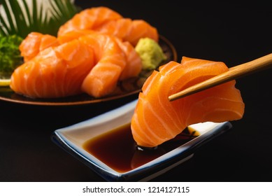 Sashimi, Salmon, Japanese food chopsticks and wasabi on the black table