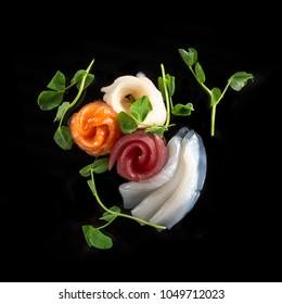 sashimi set arranged on a black background in arrangement with a knife
