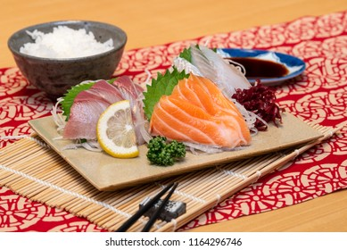sashimi set on a plate with rice and soy sauce and chopsticks
