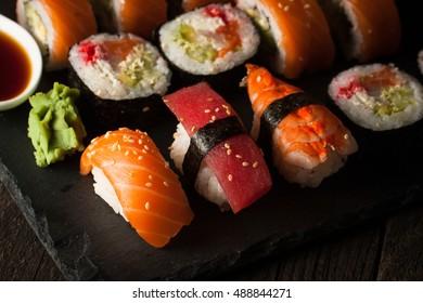 Sashimi and sushi rolls on a stone slatter. Sushi set with salmon, prawns, soy souce, wasabi and ginger.  Traditional Japanese cuisine.