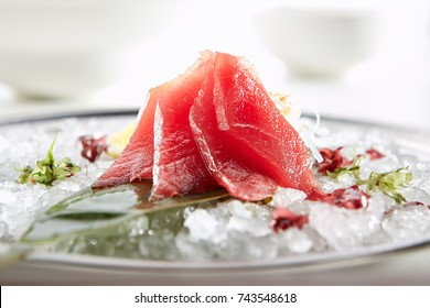Sashimi with Tuna with  slice of lemon fresh greens on bamboo leaf and in plate full of ice.