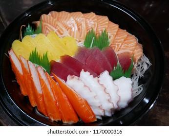 sashimi,salmon sashimi , tuna sashimi, crab sticks,squid sashimi and Tamako Sashimi, Sweet Egg served on traditional Japanese food in dish or black bowl