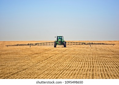 Saskatchewan farmer using a green tractor to spray his field for weeds and insects prior plowing the field and planting his spring crop of wheat or flax or soybeans or oats or other grains.