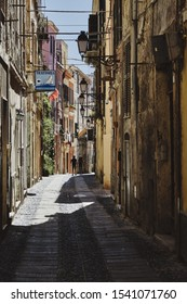 SASSARI, ITALY - Aug 16, 2019: Vertical shot of a couple in the distance walking away in an empty street of the Old Sassari in northern Sardinia, Italy