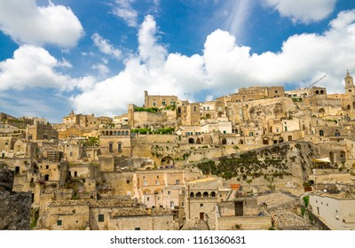 Sassi di Matera panoramic view of historical centre Sasso Caveoso of old ancient town with rock cave houses in front of blue sky and white clouds, UNESCO World Heritage, Basilicata, Southern Italy
