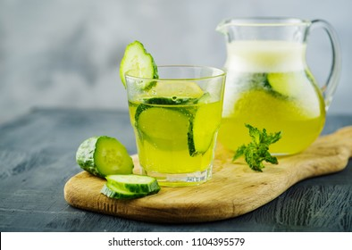 Sassy diet water. Cucumber, lemon, mint lemonade in glass and jar on wooden table.