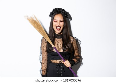 Sassy evil witch laughing and waving her broom, wearing halloween costume, standing over white background