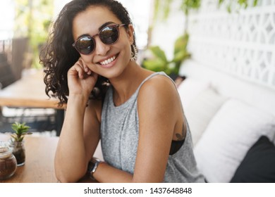 Sassy good-looking woman dark curly haircut wear glasses sitting summer patio cafe tilt head flirty smiling laughing intrigued listen story romantic date relaxing enjoying tropical hotel resort