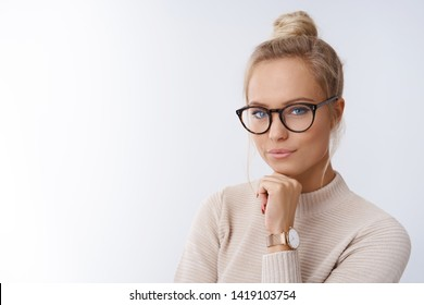 Sassy and successful good-looking accomlished female lifestyle blogger in glasses with blond hair combed holding fists under chin and looking confident at camera with daring cheeky smirk