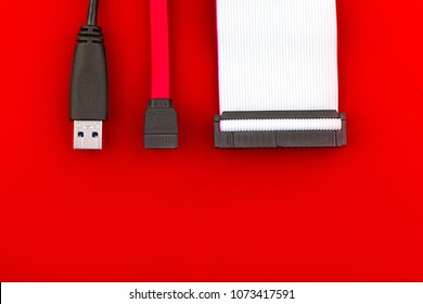 Sata cable, usb and ide cables on the red desktop. Top view. The concept of data storage