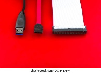 Sata cable, usb and ide cables on the red desktop.  The concept of data storage