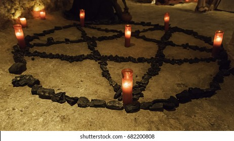 Satanic pentacle with lighted candles, dark magic ritual detail, occultism