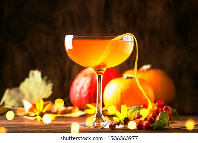 Satans whiskers, halloween cocktail with gin, vermouth, orange juice and liquor, vintage dark wooden background with festive decor