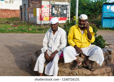 Satara / India 16 August 2018 Two Indian rural farmer Talking on Mobile Phone sitting on the side of the road at Satara Distric in Maharashtra India