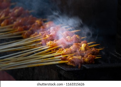 Satay being grilled with smoke and yummy looking. Satay is very popular hawker and restaurent dish as it is very delicious and very popular in Singapore, Malaysia and Indonesia.