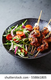 Satay chicken skewers with cherry tomatoes, red onion and fresh rocket. Home made food. Concept for a tasty and healthy meal. Black stone background. Close up.