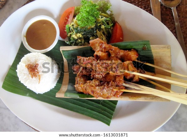 Satay with peanut sauce and rice on banana leaf