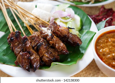 Satay or sate, skewered and grilled meat, served with peanut sauce, cucumber and ketupat. Traditional Malay food. Delicious hot and spicy Malaysian dish, Asian cuisine.