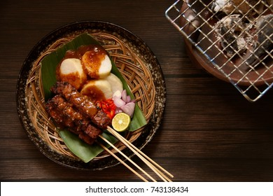 Sate Kere. Popular street food in Solo / Surakarta, Central Java. Topped with peanut sauce and accompanied with rice cake, shallots and chili pepper.