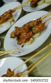 """""""sate lontong"""". A serving of meat satay accompanied by rice cake / lontong."""