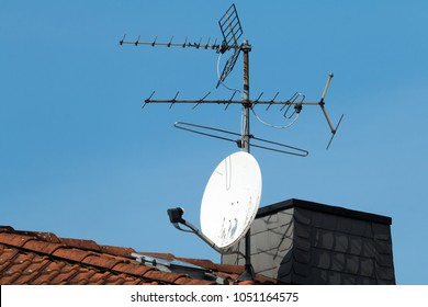 Satellite antenna and old roof antenna on a red roof