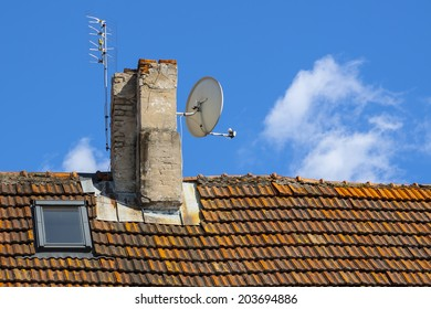 Satellite antenna on the chimney, roof of the house with tiles.