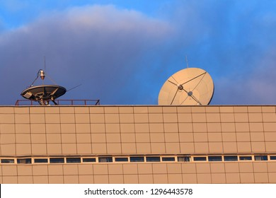 Satellite communications dishes on blue sky background