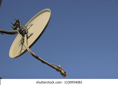 a satellite dish against the blue sky background receives a signal from space, television broadcasting
