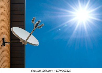 Satellite dish antenna mounted on the wall of a private house on blue sky background