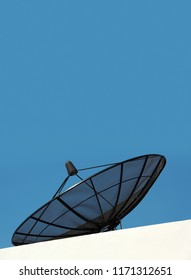 Satellite dish antenna on house roof over clear sky