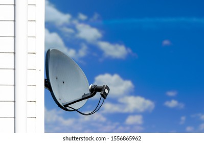 Satellite dish attached to side of house with blue cloudy sky background.