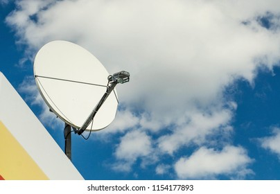 satellite dish on a background of blue cloudy sky. red satellite dish on the roof with blue sky background, for communication network or television technology