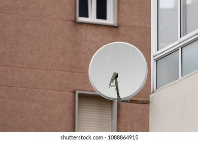 satellite dish on a building wall