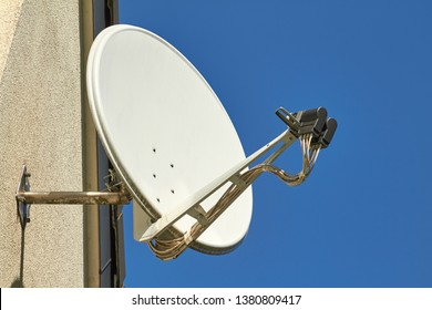 A Satellite dish on a house wall.