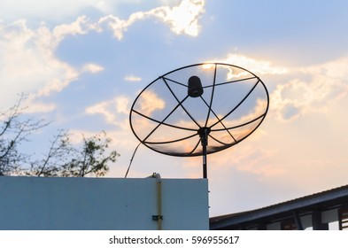 Satellite dish on roof and sunset sky
