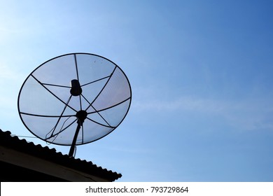 Satellite dish on the roof with sunshine and blue sky.