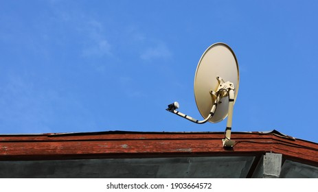 Satellite dish on roof. White metal dish and TV receiver head to view news with satellite technology. On a bright blue sky background with copy space. Choose content and focus